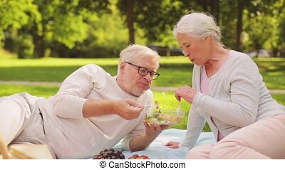 senior couple eating salad at picnic in park