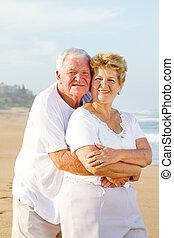senior couple embrace on beach