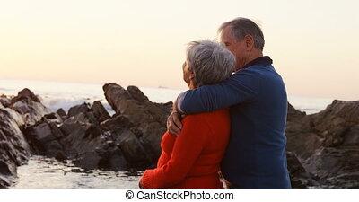 Senior couple embracing on beach 4k - Side view of senior...