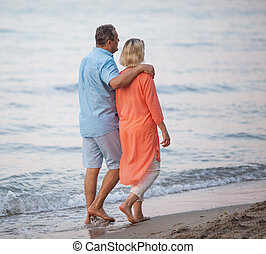 Senior couple enjoying barefoot walk at the seaside