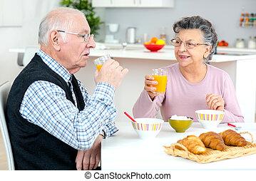 senior couple enjoying breakfast at home