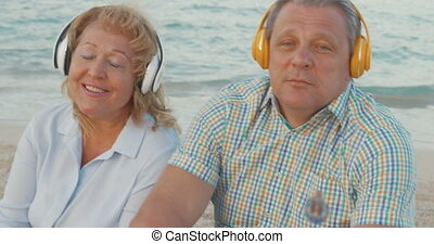 Senior couple enjoying music on the beach - Senior man and...