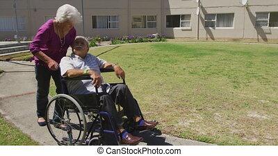 Senior Caucasian woman walking with a senior Caucasian man sitting on a wheelchair in a park of a retirement home during a sunny day.