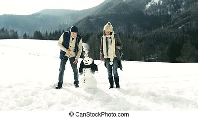 Senior couple enjoying themselves in winter nature. -...