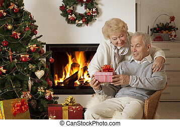 Senior couple exchanging Christmas gifts
