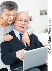 senior couple excited in seeing family members on the internet