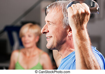 Senior couple exercising in gym - Senior couple - man and...