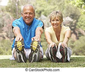 Senior Couple Exercising In Park