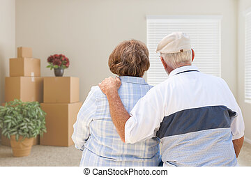 Senior Couple Facing Empty Room with Packed Moving Boxes and Potted Plants