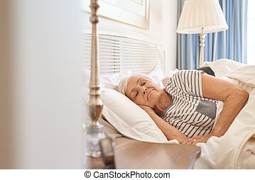 Senior couple fast asleep together in their bed