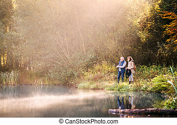 Senior couple fishing at the lake in autumn. - Active senior...