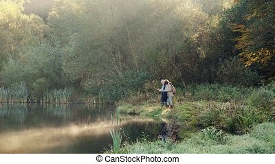 Senior couple fishing at the lake in autumn. - Active senior...