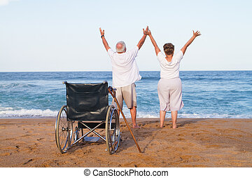 a senior couple with their arms stretched upwards and a wheelchair in the background depicting free from illness