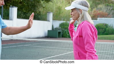 Senior couple giving high five in tennis court 4k - Happy...