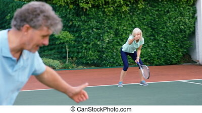Senior couple giving thumps up to each other while playing tennis 4k