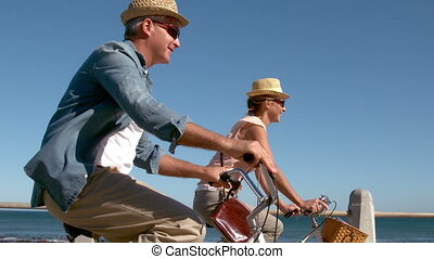 Senior couple going on a bike ride on the pier in slow...