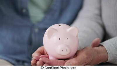 senior couple hands with coin and piggy bank - family,...