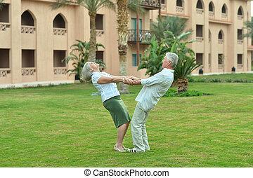 Senior couple have fun at tropic hotel garden