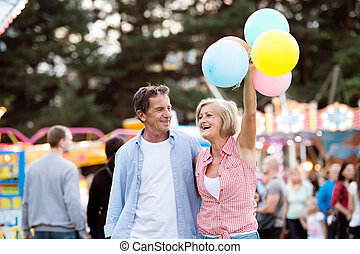 Senior couple having a good time at the fun fair. Woman...