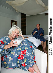 senior couple having breakfast in a hotel room