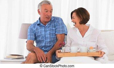 Senior couple having breakfast on the bed