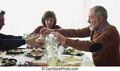 Senior couple having dinner with friends at home.