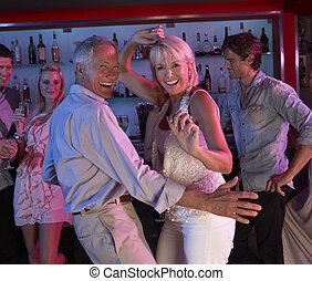 Senior Couple Having Fun In Busy Bar