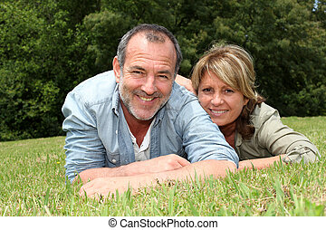 Senior couple having fun laying in grass