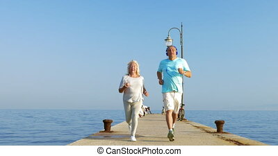 Senior couple having morning jog with music - Steadicam shot...