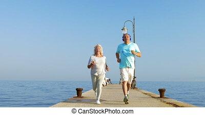 Senior couple having morning jog with music