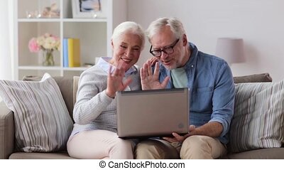 senior couple having video chat on laptop at home - family,...
