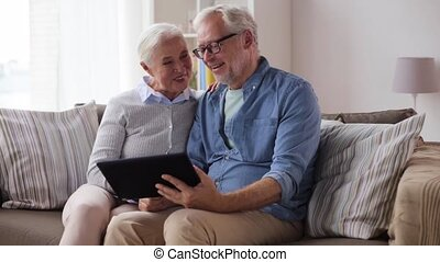 senior couple having video chat on tablet pc - communication...