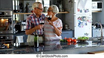 Senior couple having wine in kitchen 4k