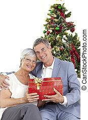 Senior couple holding a Christmas present