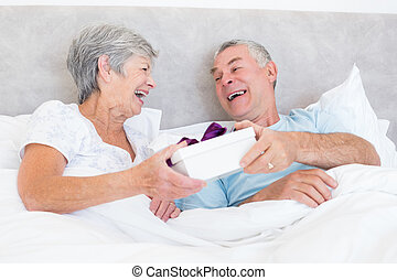 Senior couple holding gift box in bed