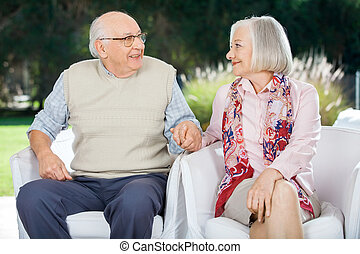 Senior Couple Holding Hands And Looking At Each Other -...