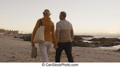 Senior couple holding hands at beach