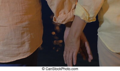 Senior couple holding hands by the sea at night