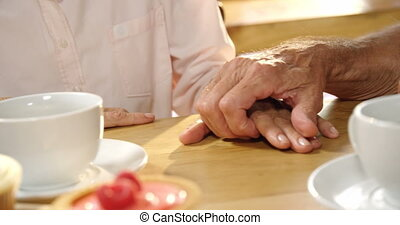 Senior couple holding hands on cafe table 4k