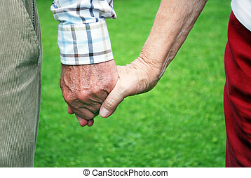 senior couple holding hands with green background