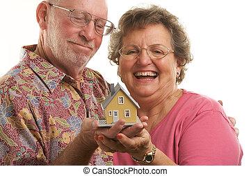 Senior Couple & Home - Happy Senior Couple holding a model...