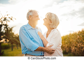 Senior couple hugging each other outdoors during sunset