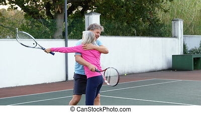 Senior couple hugging on tennis court 4k