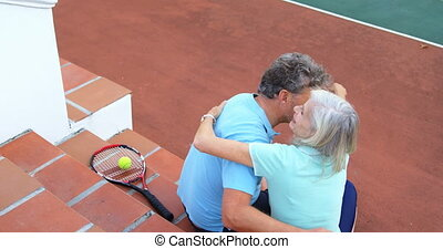 Senior couple hugging on tennis court stairs 4k - Romantic...