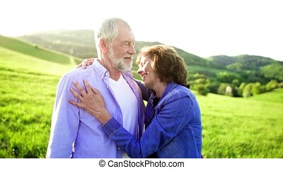 Senior couple hugging outside in spring nature. - Happy...