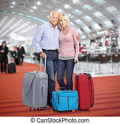 Senior couple in airport. Holiday travel background.