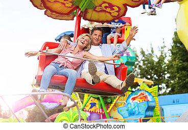 Senior couple in amusement park - Senior couple having fun ...