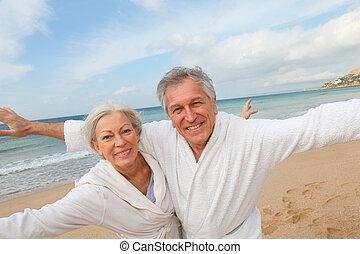 Senior couple in bathrobe at the beach