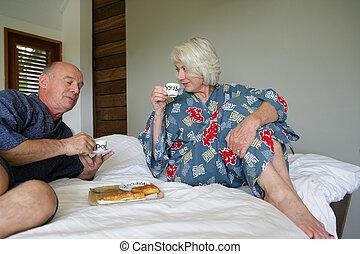 Senior couple in bathrobe sitting on a bed having breakfast