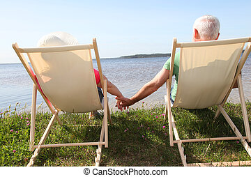 Senior couple in deck chairs in front of a lake